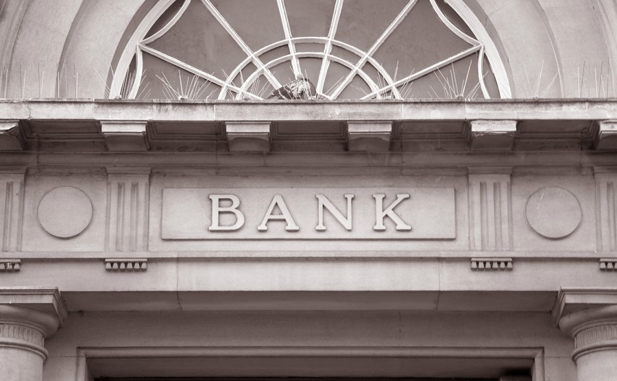 bank-sign-over-entrance-door-in-black-and-white-sepia-tone