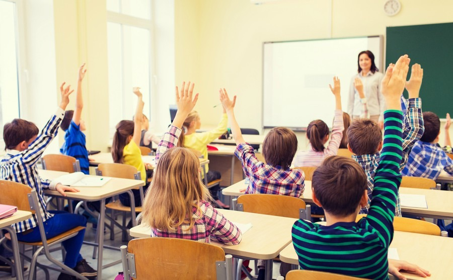 education-elementary-school-learning-and-people-concept-group-of-school-kids-with-teacher-sitting-in-classroom-and-raising-hands