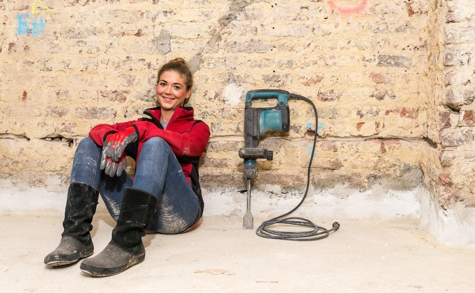 smiling craftswoman sitting on the floor against brick wall needing French property renovation