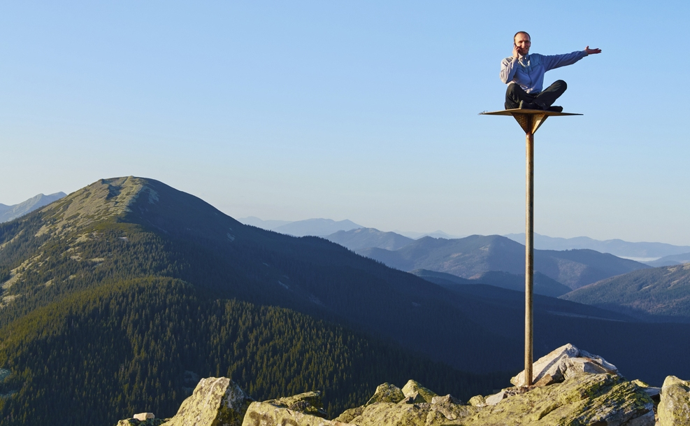 Man sitting on pole