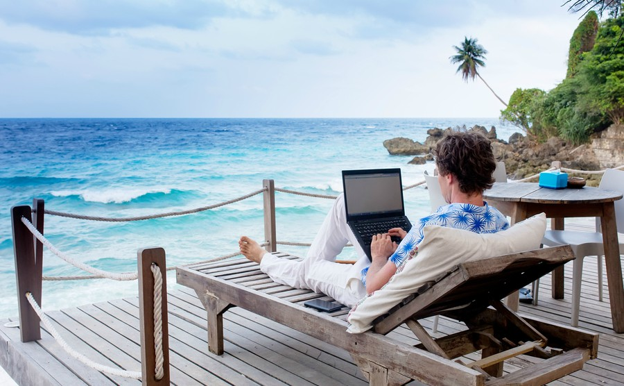 man-with-laptop-and-mobile-phone-running-remotely-on-colorful-beach-of-island-among-the-palms-cafe