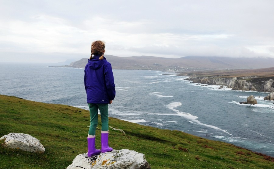girl-standing-on-a-stone-in-the-background-dramatic-coastline-of-achill-island-county-mayo-ireland