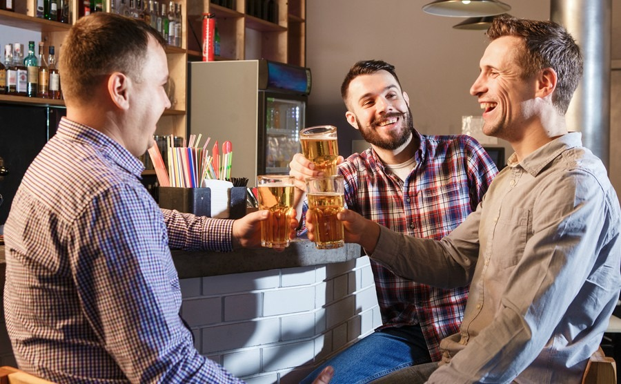 happy-friends-drinking-beer-at-counter-in-pub
