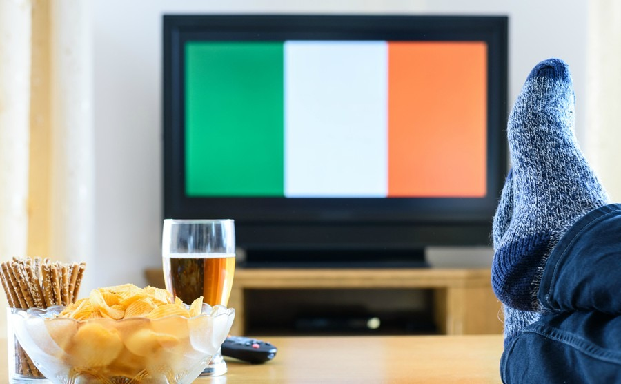 man-watching-irishireland-flag-on-tv-screen-with-legs-on-table-stock-photo