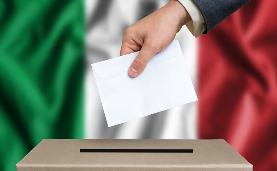 election-in-italy-the-hand-of-man-putting-his-vote-in-the-ballot-box-italian-flag-on-background
