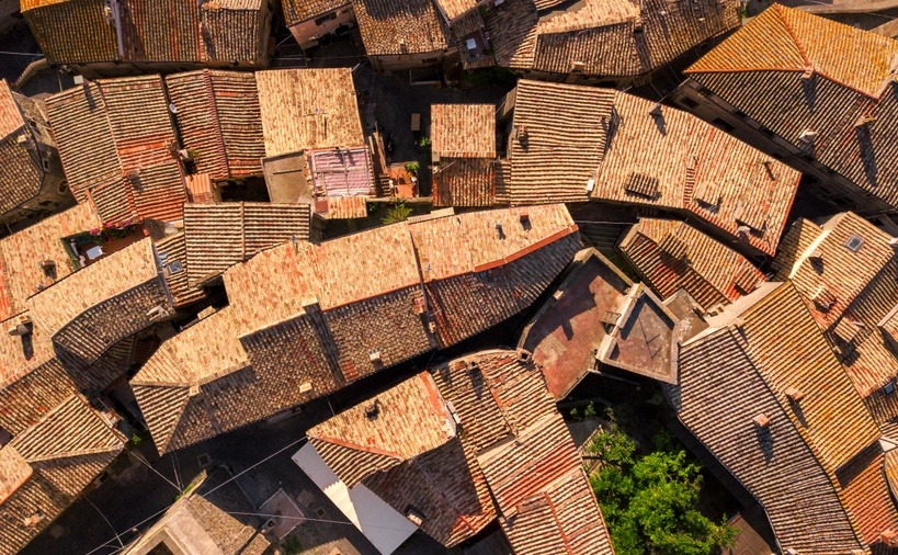 Perpendicular aerial view of red tile roofs of a small Italian mountain village.