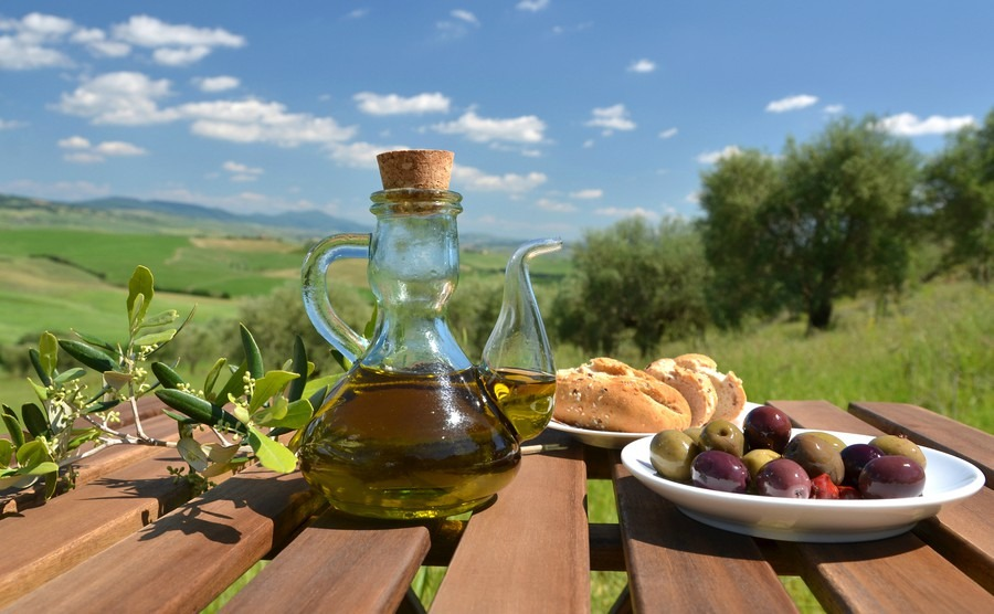 olive-oil-olives-and-bread-on-the-wooden-table-against-tuscan-landscape-italy