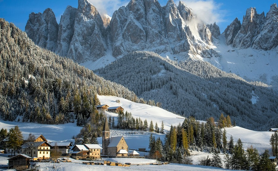 the-small-village-of-st-magdalena-or-santa-maddalena-with-its-church-covered-in-snow-and-with-the-odle-or-geisler-dolomites-mountains-in-the-val-di-funes-valley-in-south-tyrol-in-italy-in-winter