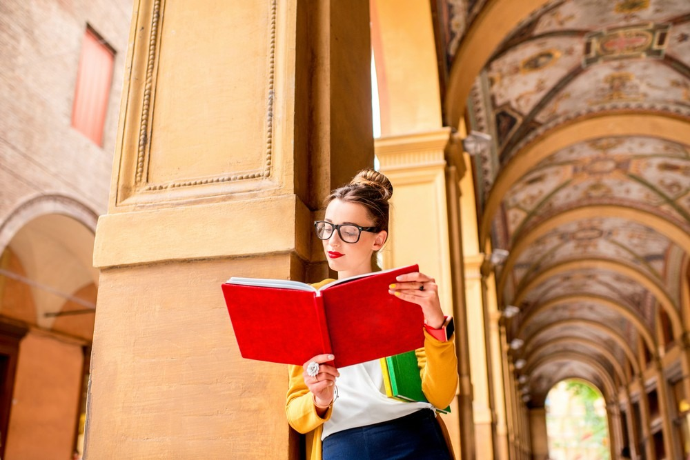 Young female student dressed casually standing with books in the famous arched galleries in Bologna city in Italy. Bologna is a student city and home to the oldest university in the world