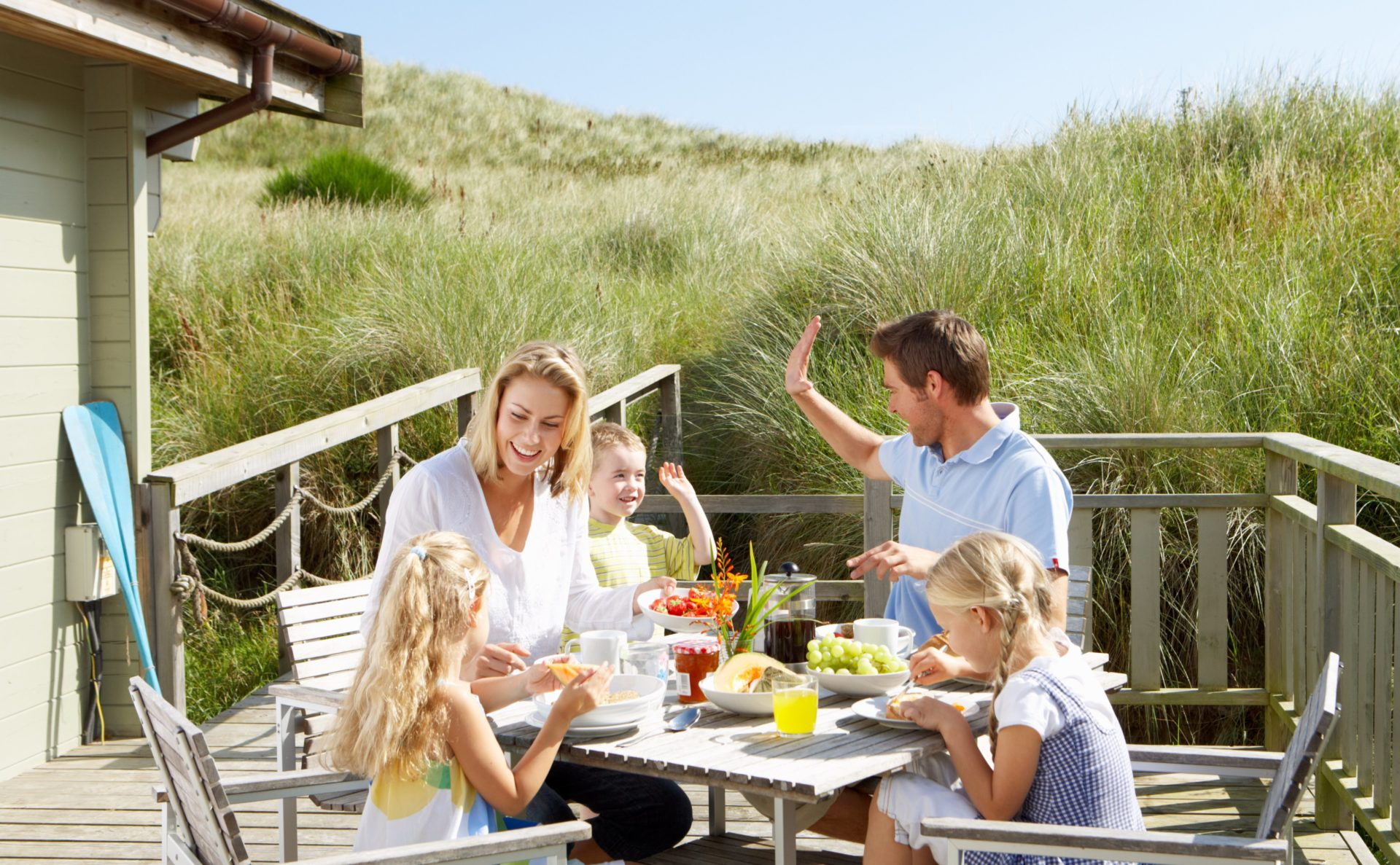 Family eating together on holiday | Buying a holiday home with family