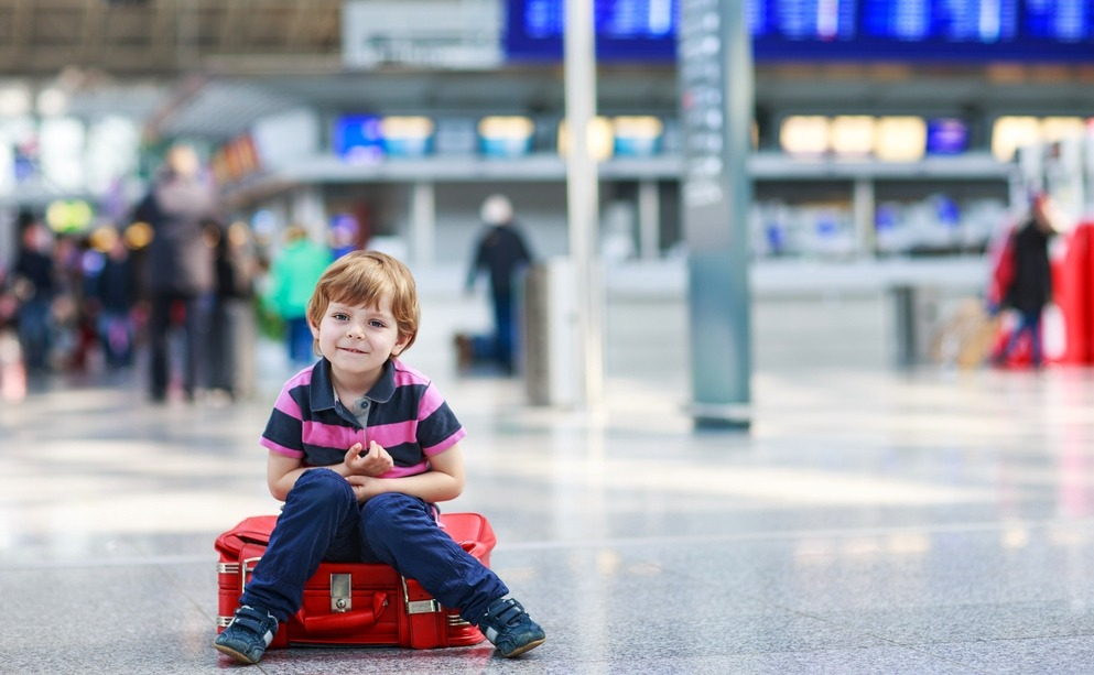 Blond boy of 4 years sitting on suitcase at the airport