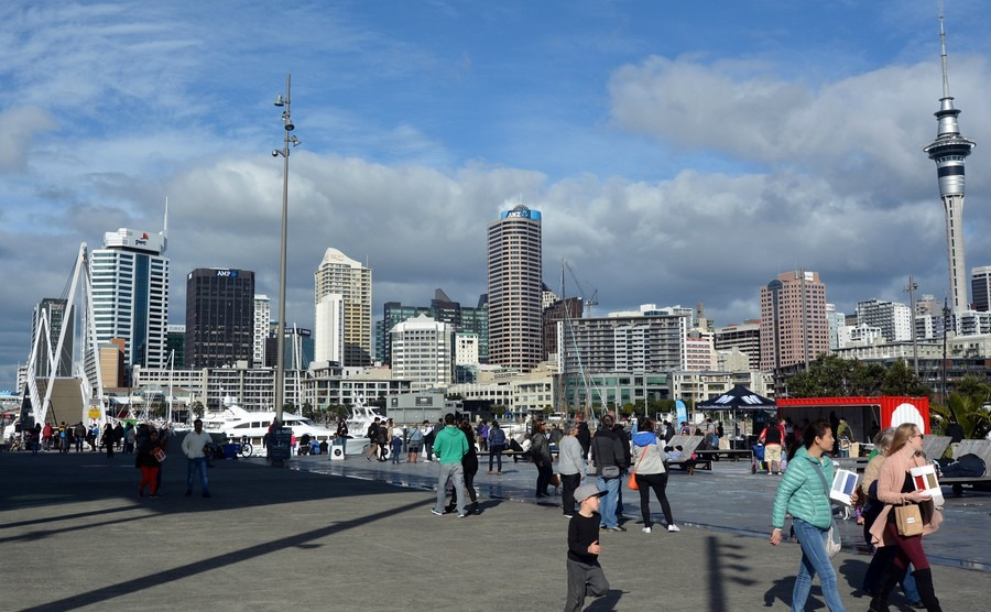 visitors-walks-at-wynyard-quarter-against-auckland-skyline-new-zealand-auckland-is-one-of-the-most-ethnically-diverse-cities-in-the-world