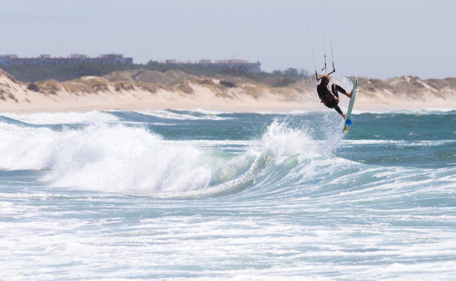 man jumps on kite surf board sea waves in Cabedelo Beach, Viana do Castelo, Portugal.