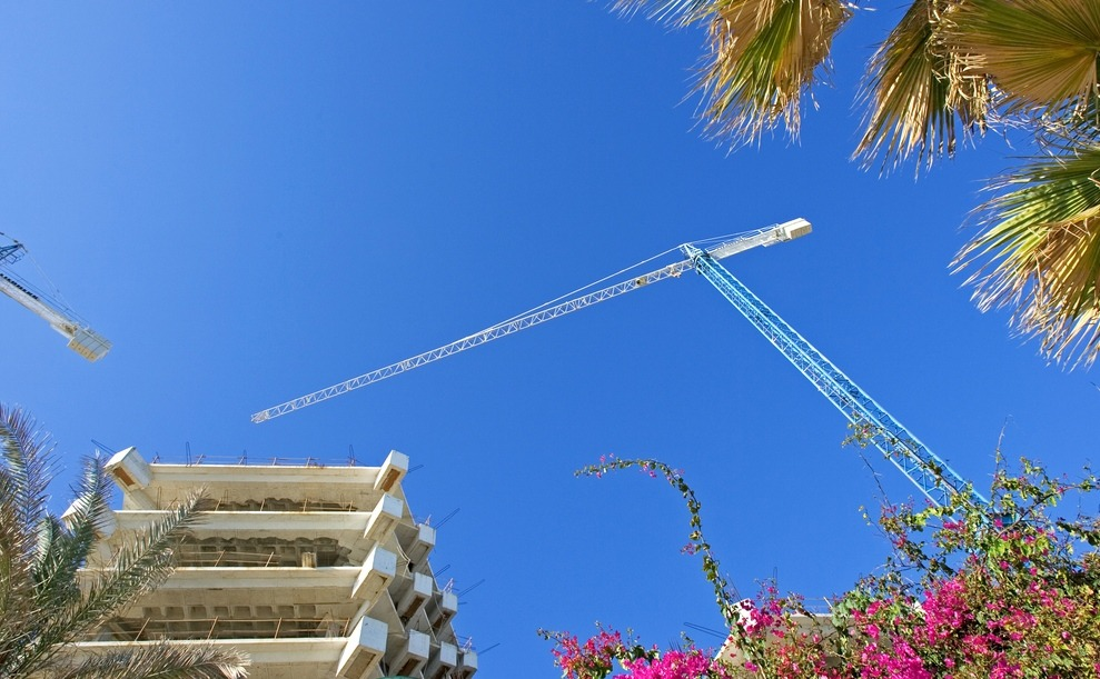 Cranes, buildings and flowers against a deep blue sky in Spain