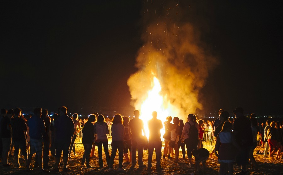 laredo-spain-june-24-2014-people-celebrate-st-johns-eve-around-a-bonfire-in-a-beach-in-northern-spain-st-johns-eve-celebration-around-a-bonfire-is-reminiscent-of-midsummers-pagan-rituals