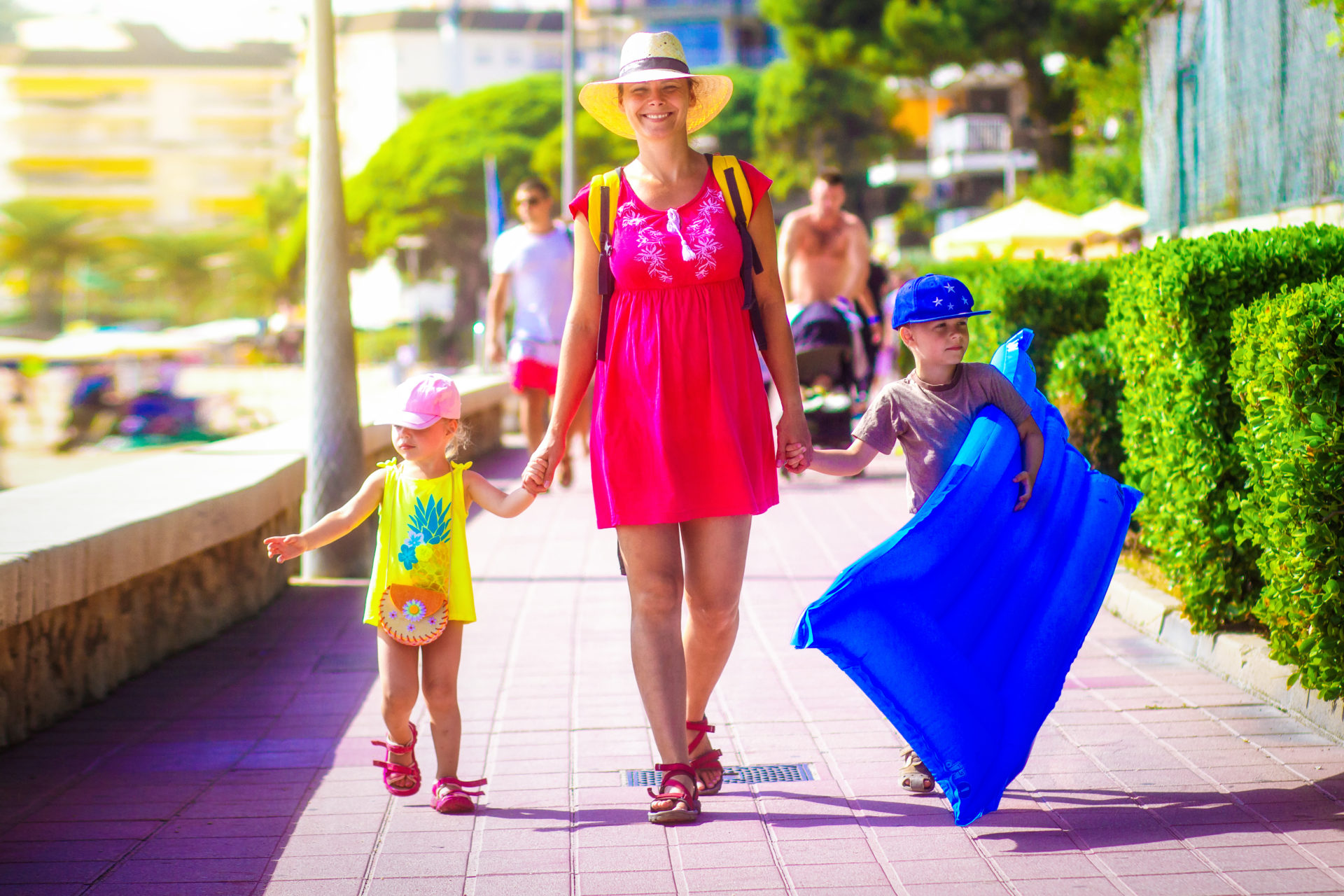 Mother and young children walk along Spanish seafront in sunshine