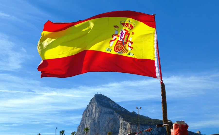 national-flag-of-spain-from-back-side-fluttering-in-wind-the-rock-of-gibraltar-in-background