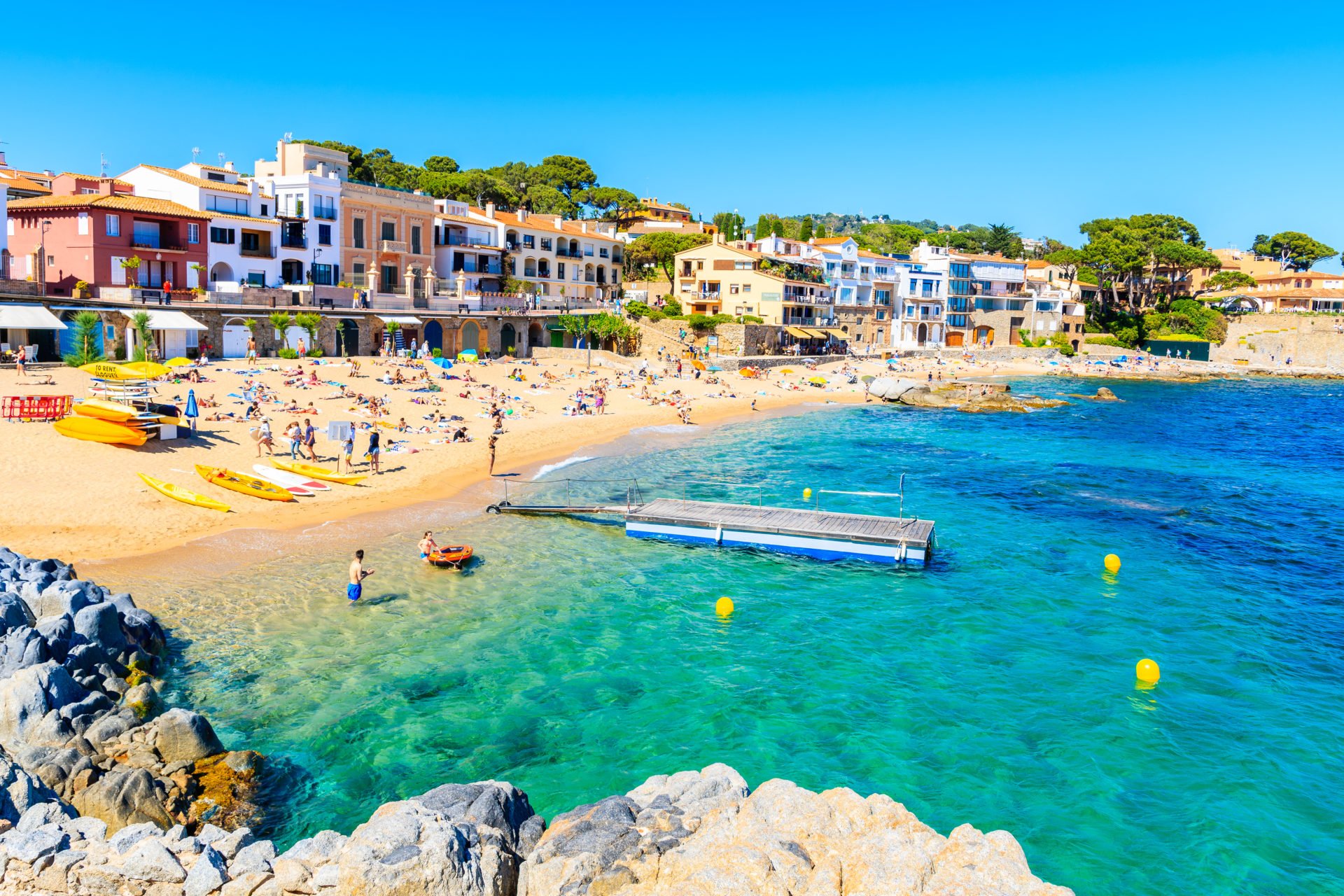 People in water on beach in village of Calella de Palafrugell, Costa Brava, Spain